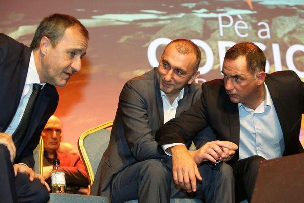 Meeting nationaliste en 2017. Gilles Simeoni (D) actuel président du conseil exécutif de Corse en conversation avec Jean-Guy Talamoni (G), président de l'Assemblée de Corse, sous le regard de Jean-Christophe Angelini.
