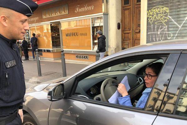 Un policier contrôle une automobiliste en règle place Castellane, à Marseille.