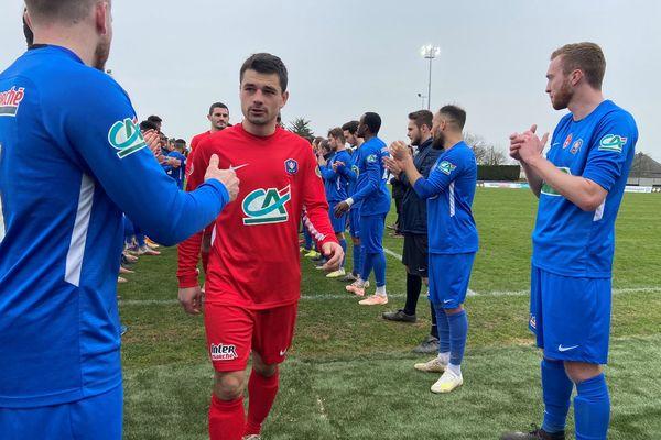 Haie d'honneur pour les joueurs de Guichen (en rouge) à la fin de leur match contre l'Olympique Saumur FC