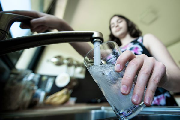 Une femme remplit un verre d'eau au robinet.