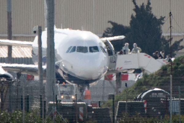 Les français descendent de l'avion, atterri à Istres à 13H30. Ils portent tous un masque sanitaire.