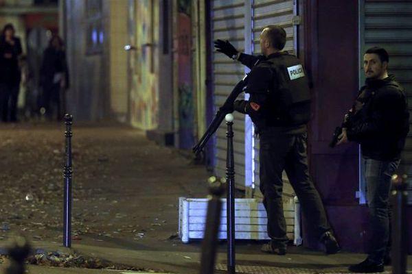 Un policier demande à des passants de se mettre à l'abri à Paris vendredi 13 novembre 2015.