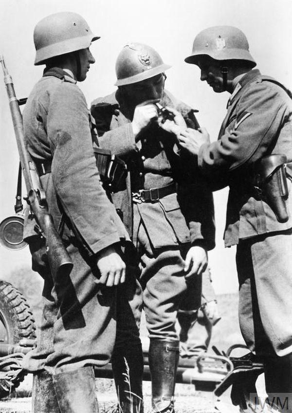 Des soldats allemands donnant une cigarette à un soldat belge en mai 1940.
