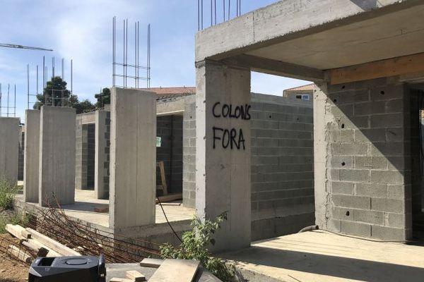 """A Linguizzetta en Haute-Corse, les Marina di Bravone  en construction portent l'inscriptions """"colons fora"""". Le projet est accusé par certains nationalistes d'encourager la spéculation immobilière. Notamment grâce à des outils de défiscalisation."""