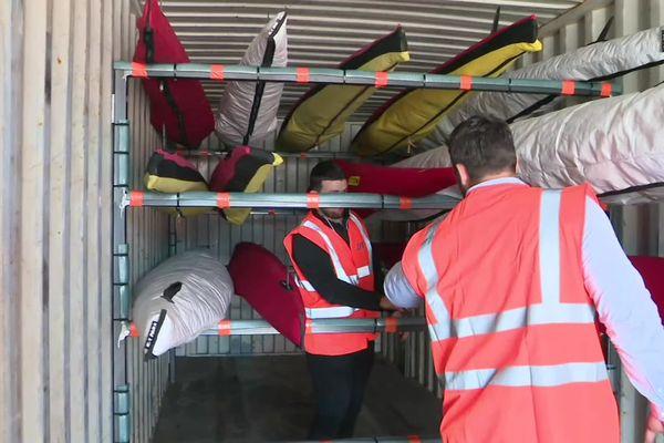 17 canoë-kayaks et du matériel d'entraînement sont chargés dans le container aux couleurs de la Fédération Française de Canoë-Kayak