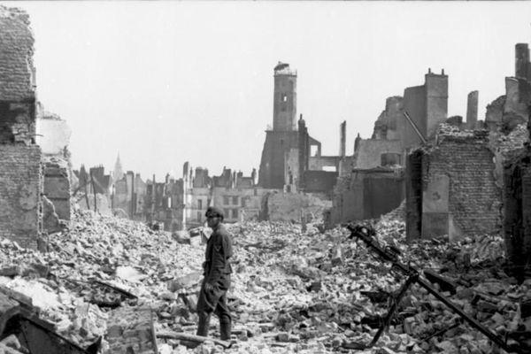 Un soldat allemand dans les ruines de Calais en mai 1940. En arrière-plan, la Tour du Guet qui a résisté aux bombardements.
