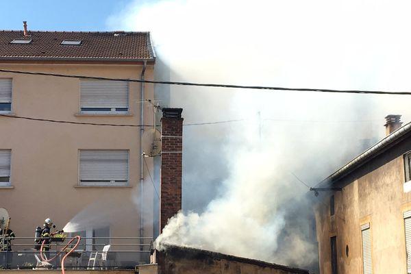 Les sapeurs-pompiers tentent d'empêcher la propagation du feu aux habitations attenantes.