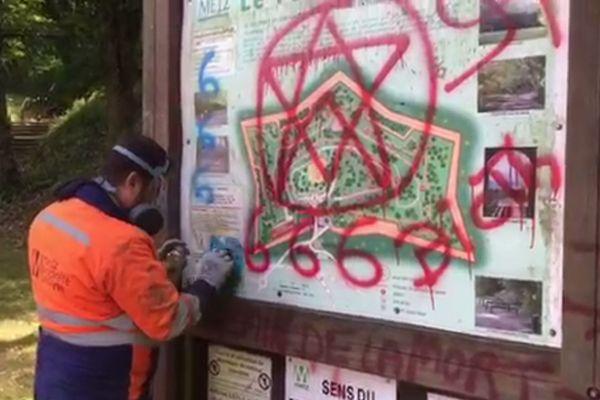Les ouvriers municipaux nettoient les graffitis nazis et satanistes sur l'entrée du Fort