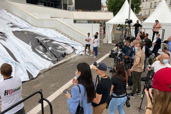 Journalistes et promeneurs admirent ce moment presque cérémonial de l'installation de l'affiche d'un festival tant attendu après des mois de crise sanitaire.