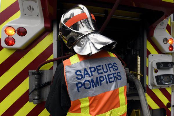 Pompier en tenue pour éteindre un feu, image d'illustration