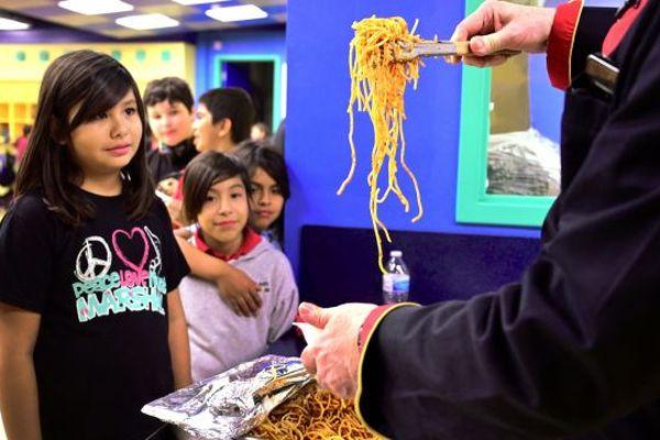 Le chef Bruno Serato sert des spaghettis aux enfants, dont certains issus de milieux sans abri, dans le cadre d'un programme de clubs pour garçons et filles après l'école, situé à Anaheim en Californie.