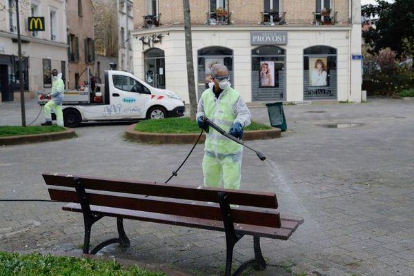 Un agent de la propreté désinfecte un banc à Suresnes (Hauts-de-Seine).