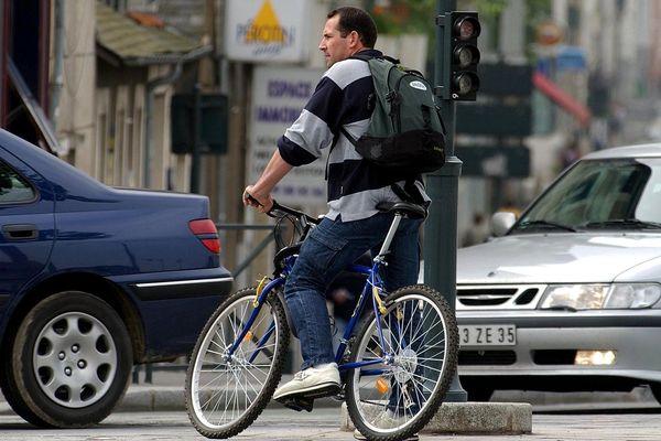 Un cycliste au milieu des voitures - Photo d'illustration
