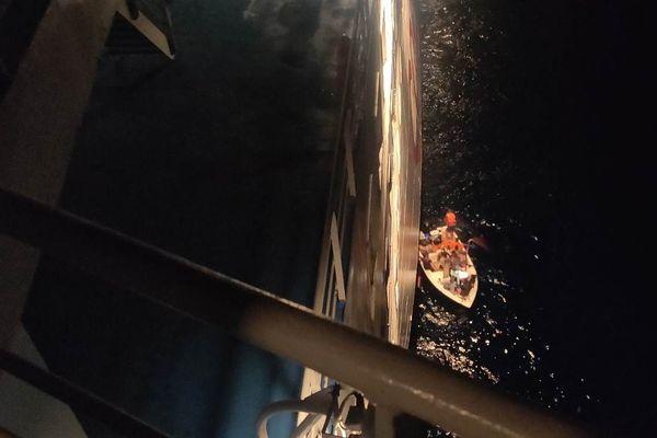 La frêle embarcation tente de se rapprocher suffisamment du navire de la Corsica Linea pour que ses passagers puissent y être hissés