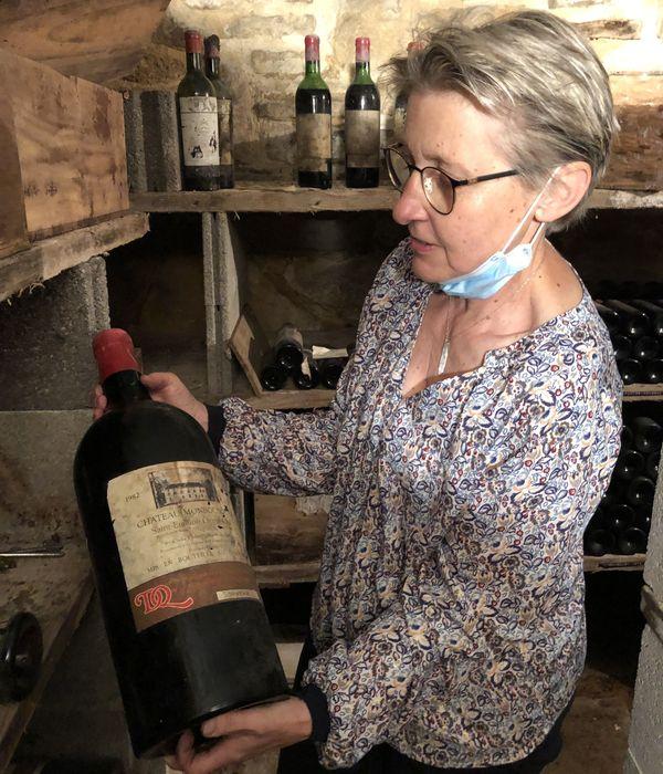 Caroline Turin tient en mains une bouteille de 5 litres de vin de Saint-Emilion
