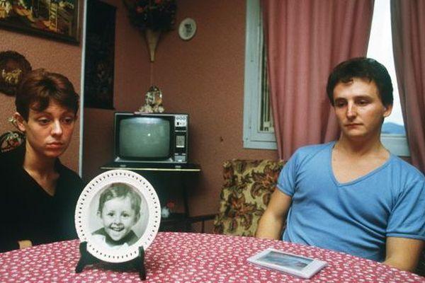 Désemparés, Christine et Jean-Marie Villemin, les parents du petit Grégory, 4 ans, retrouvé noyé le 16 octobre 1984, pieds et poings liés dans la Vologne, sont assis, le 23 novembre 1984, autour de la table de leur salle-à-manger sur laquelle est posée une assiette à l'effigie de leur enfant.