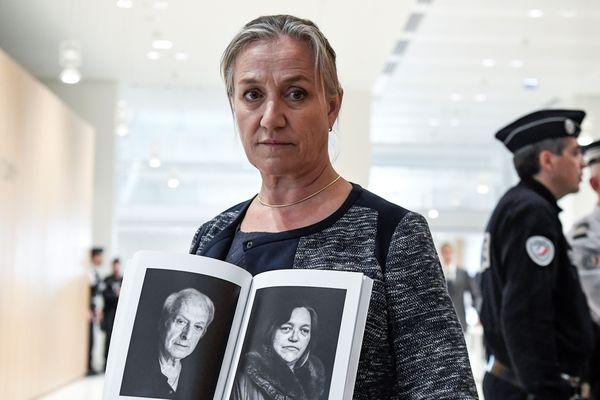La DR Irène Frachon tenant les portraits de deux victimes du Médiator.