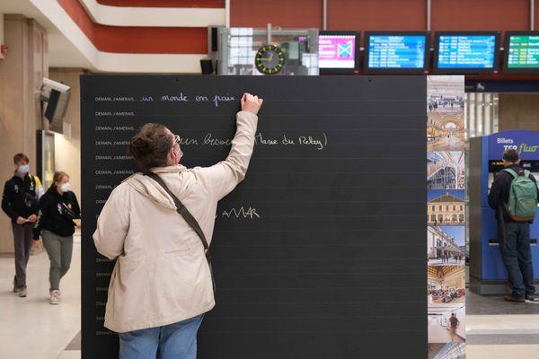 """Un voyageur complète à la craie le début de phrase """"Demain j'aimerais..."""", sur le tableau noir installé dans le hall de la gare de Mulhouse."""