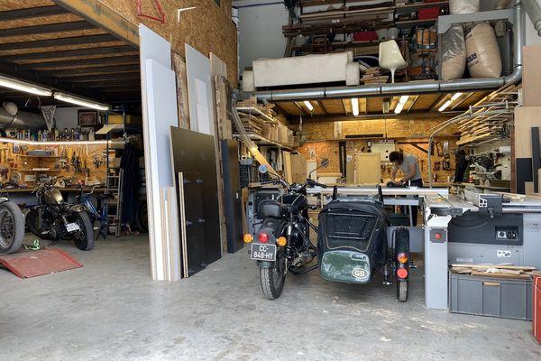 Nicolas Dutouron fabrique du mobilier en bois au fond de son atelier entouré de motos.