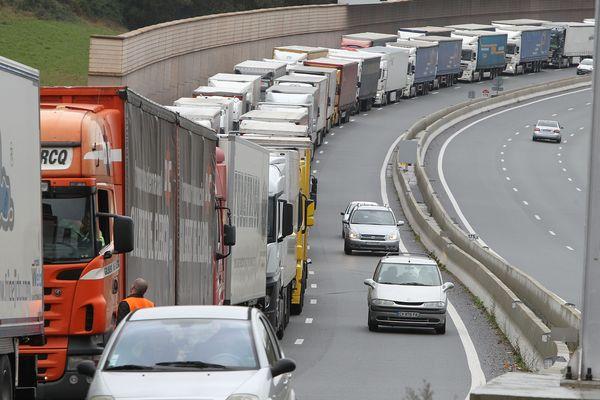 """Des barrages organisés par les transporteurs routiers su syndicat """"OTRE """", décembre 2013. Des files de camions étrangers sont arrêtées sur l'autoroute et la circulation des voitures ne se fait que sur une file."""