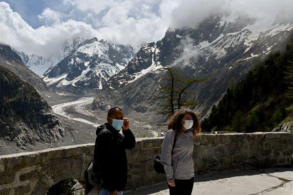 Des touristes portent le masque devant la Mer de glace dans le massif du Mont-Blanc, le 16 mai 2020.