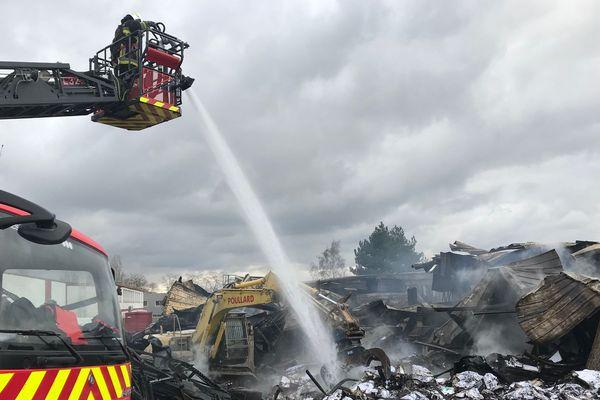 Les pompiers continuent d'arroser la masse de papier sous laquelle le feu couve.