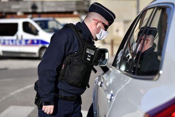 Un policier, équipé d'un masque, effectue un contrôle.