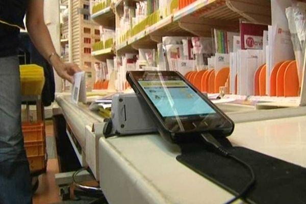 Un facteur du centre de distribution de Chinon (Indre-et-Loire) recharge son smartphone avant de partir en tournée