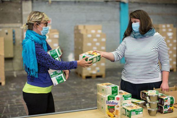 Marielle et Marguerite préparent de colis pour bébés dans l'entrepôt de l'association MaMaMa