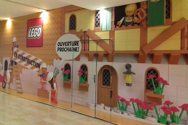 Au rez-de-chaussée des Halles de Strasbourg, une palissade dissimule l'aménagement en cours du futur Lego Store. Clin d'oeil à l'Alsace : colombages, bretzel...
