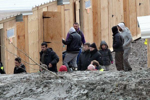 Des migrants accompagnés par des membres d'associations arrivent au camp de Grand-Synthe dans le nord de la France, le 7 mars 2016