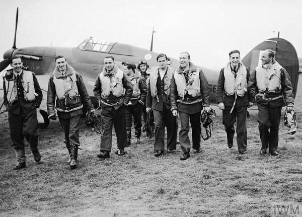"""Les pilotes du 303 Squadron à Leconfield, le 24 octobre 1940. Au premier plan de gauche à droite : Mirosław Feric, John Kent, Bogdan Grzeszczak, Jerzy Radomski, """"Tolo"""" Łokuciewski, Zdzisław Henneberg, Jan Rogowski et Eugeniusz Szaposznikow. Au centre, en arrière-plan, le pilote avec le casque est Jan Zumbach."""