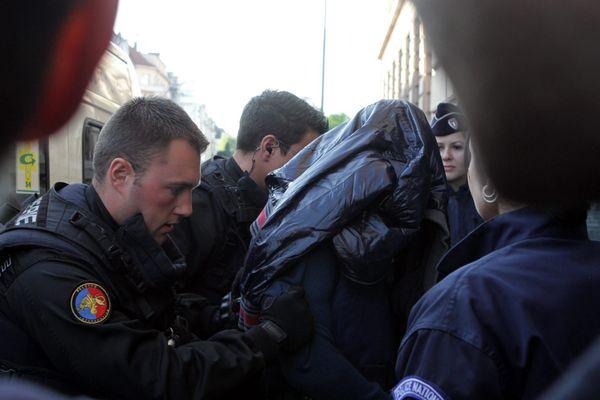 Sofiane Hambli, le visage recouvert d'un blouson, lors de son arrivée au Tribunal de Mulhouse en octobre 2013