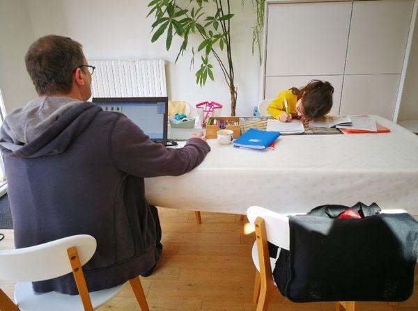 Pascal et Capucine s'installent sur la table de la pièce principale pour faire l'école à la maison.