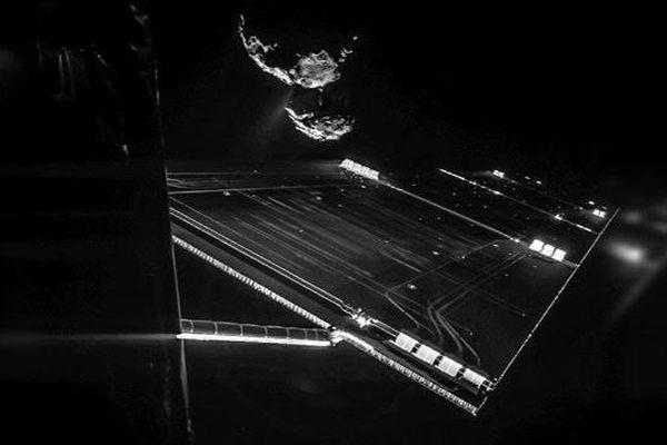 Vue partielle sur l'un des panneaux solaires de la sonde Rosetta. En arrière-plan, la comète Tchourioumov-Guérassimenko, située à plusieurs centaines de millions de kilomètres de notre planète et sur laquelle repose le robot Philae.