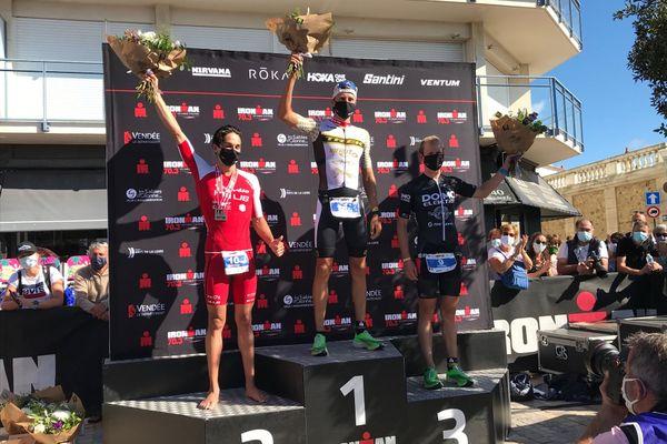 sur le podium les trois gagnants brandissent leur trophée et portent leur masque