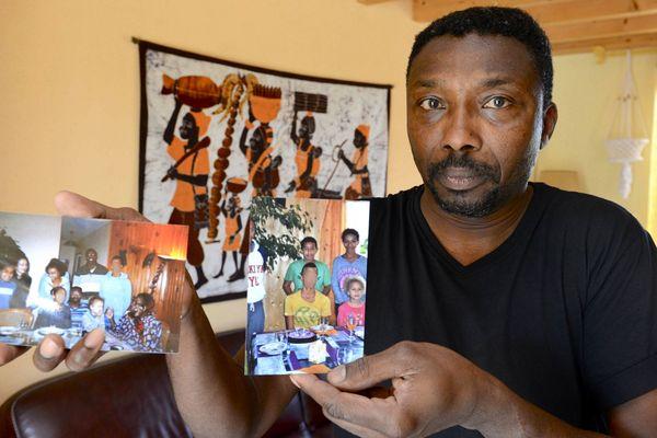 Le frère du père de famille victime du crash présentant des photos des 7 membres de sa famille morts au nord du Mali.