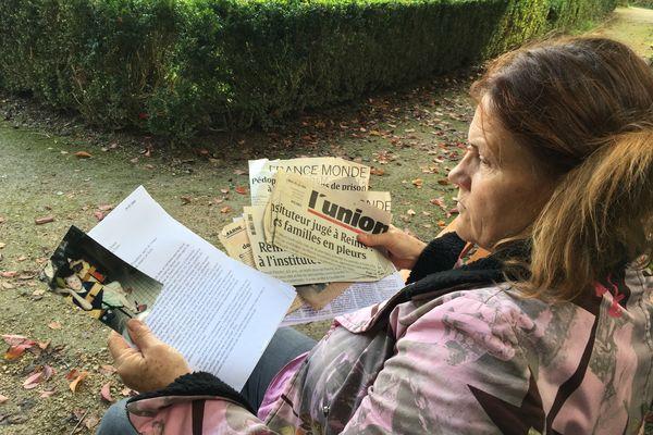 Anne Van Wymeersch tenant des coupures de presse sur l'affaire, la copie de sa plainte, et une photographie de son fils Nils.