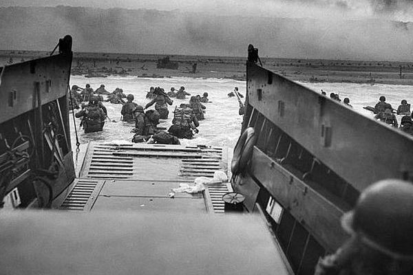 Photo intitulée « Entre les dents de la mort. Les troupes américaines pataugent dans l'eau sous les balles nazies. ». Photo prise vers 08:30 le matin du 6 juin 1944.