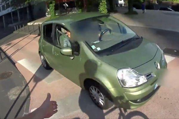 La main du cycliste montre clairement que la voiture a largement dépassé le stop sans marquer de temps d'arrêt.