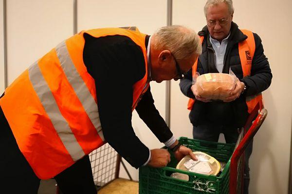 Alain et Philippe, bénévoles pour les Banques Alimentaires récoltent des produits du concours général agricole pendant le Salon de l'agriculture