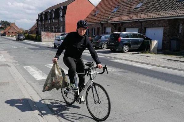 Romain Roussel, à vélo, avec un sac de déchets.