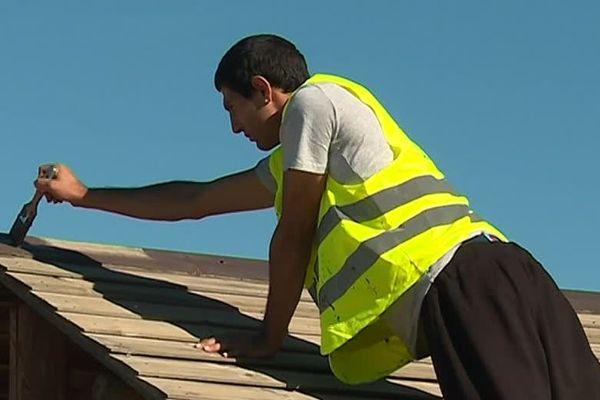 """A l'occasion d'un chantier de réinsertion organisé par l'association """"Réduire les Risques"""", les jeunes travailleurs ont l'objectif de repeindre des panneaux d'affichage, dans les jardins partagés de Malbosc à Montpellier. Octobre 2018."""