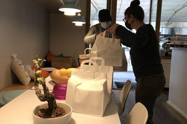 Typhaine Miss distribue les sacs à emporter aux clients.