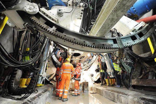 Des ouvriers sur le chantier de construction du futur TGV Lyon-Turin devant le grand tunnelier TBM utilisé pour l'excavation du tunnel de la ligne ferroviaire.