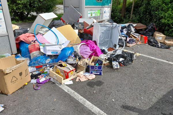 Des déchets s'amassent près des conteneurs poubelles de la place.