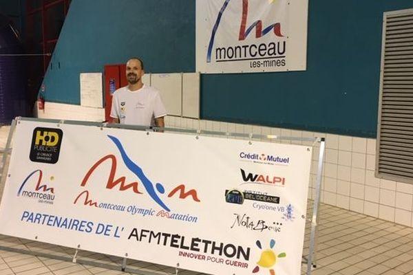 Gilles Grabski pose devant une affiche du Téléthon à la piscine de Montceau-les-Mines.