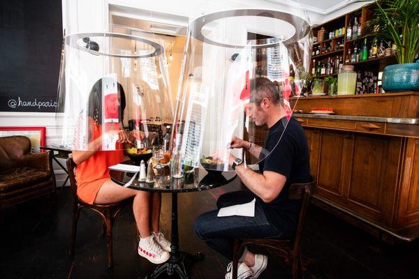 """Deux personnes au restaurant sous cloche, derrière du plexiglas à Paris chez H.A.N.D. pour éviter toute contamination. Dans le Grand Est, on pourrait aisément dire qu'ils sont """"nareux""""."""