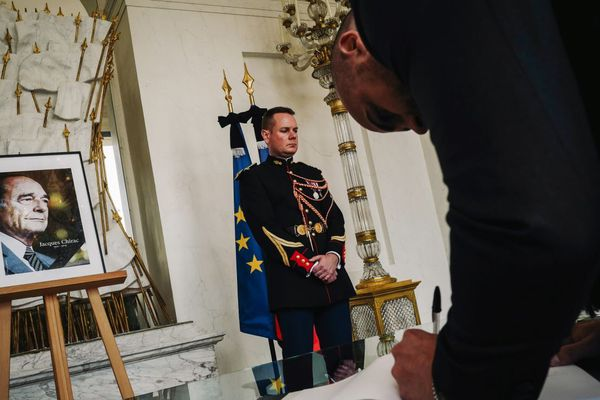 Un citoyen, ce samedi, en train de signer le registre installé en mémoire de Jacques Chirac à l'Elysée.