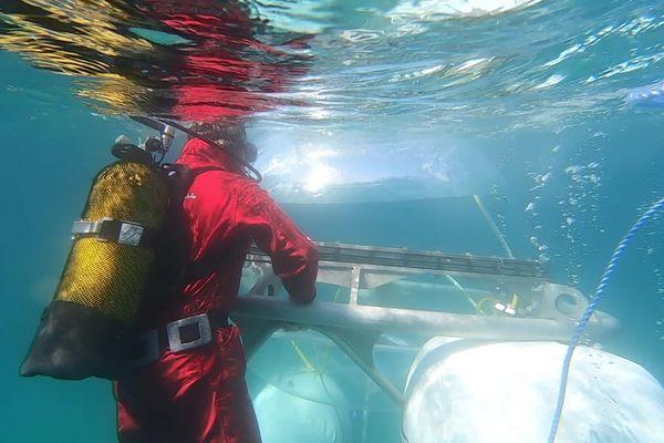 Un plongeur s'affaire autour de l'Aquabulle afin de l'immerger.